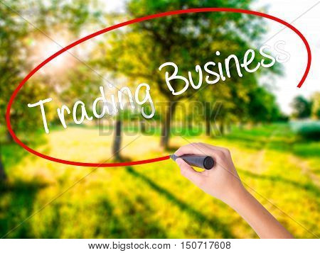 Woman Hand Writing Trading Business With A Marker Over Transparent Board .