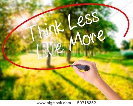 Woman Hand Writing Think Less Live More With A Marker Over Transparent Board