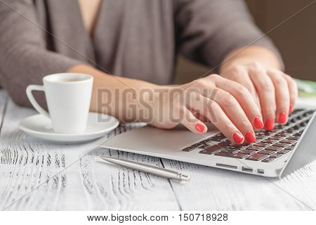 Adult Single Female Sitting At Table Holding Coffee Cup And Typing On Laptop With Light Flare Coming