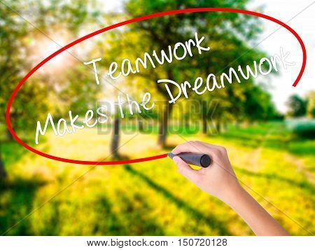 Woman Hand Writing Teamwork Makes The Dreamwork With A Marker Over Transparent Board
