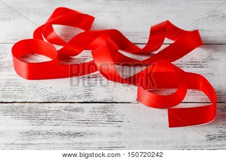 Shiny red ribbon on white wooden background