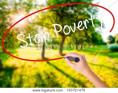 Woman Hand Writing Stop Poverty  With A Marker Over Transparent Board