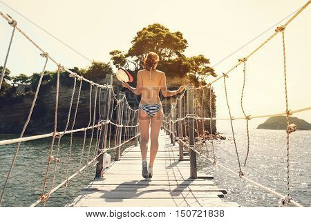 Young beautiful woman in swimsuit walking on a wooden bridge to the island. Travel Art Lifestyle Photo. Zakynthos Greece.