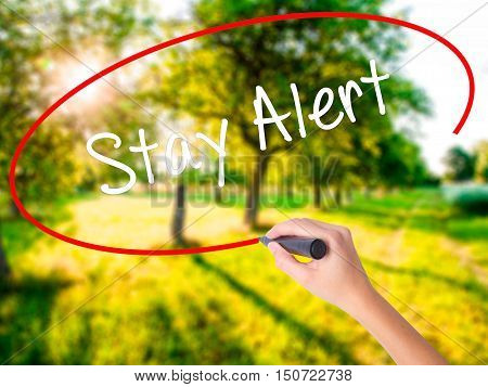 Woman Hand Writing Stay Alert With A Marker Over Transparent Board
