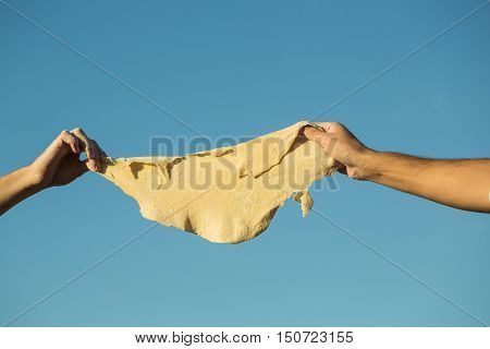 Hands of man cook chefs stained with flour tear the dough on blue sky background