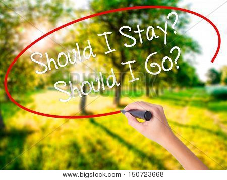 Woman Hand Writing Should I Stay? Should I Go? With A Marker Over Transparent Board