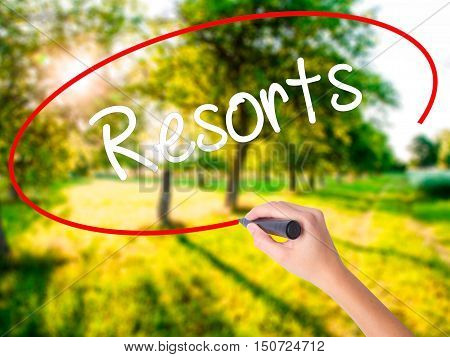 Woman Hand Writing Resorts  With A Marker Over Transparent Board