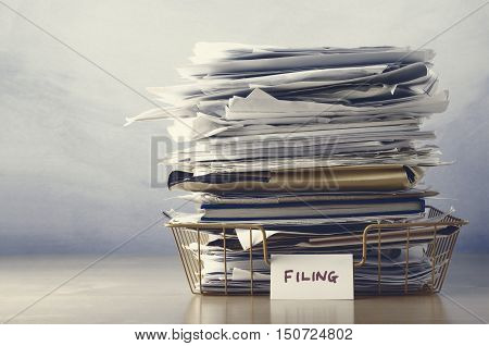 Filing Tray Piled High With Documents In Drab Hues