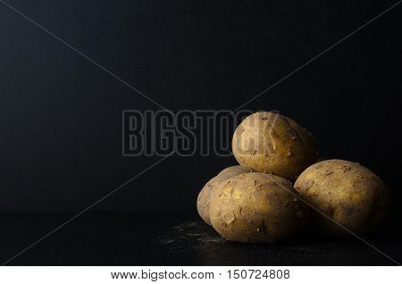 Whole, Unpeeled Potatos On Black With Soil