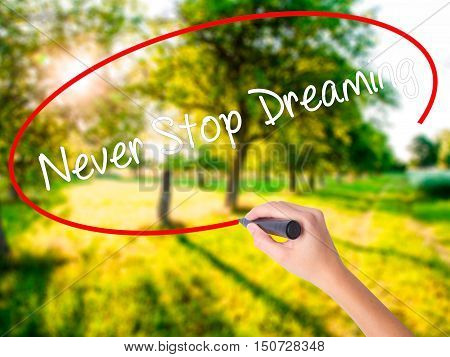 Woman Hand Writing Never Stop Dreaming With A Marker Over Transparent Board
