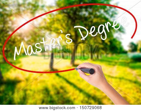 Woman Hand Writing Master's Degree With A Marker Over Transparent Board .