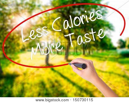 Woman Hand Writing Less Calories More Taste With A Marker Over Transparent Board