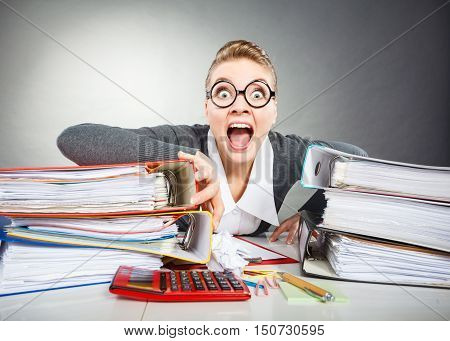 Facial expressions during work. Crazy scared accountant businesswoman surrounded by documents and binders in office.