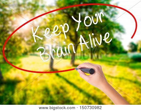 Woman Hand Writing Keep Your Brain Alive With A Marker Over Transparent Board