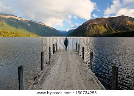 Woman Standing on Dock End on Lake Rotoiti. Nelson Lakes National Park, St Arnaud, New Zealand