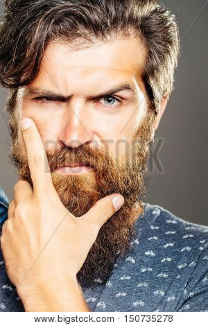 Handsome man serious hipster with long beard moustache and raised eyebrow on grey background