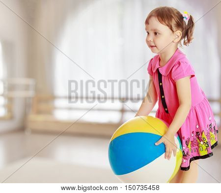 Beautiful little girl in a pink dress throwing a big striped ball. Turned sideways. Close-up.On the background of the great hall of the kindergarten with a semicircular window.