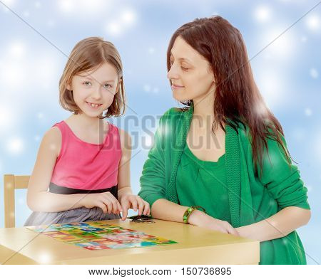 Clever little girl and her teacher at the table laid out cards with pictures.Blue Christmas festive background with white snowflakes.