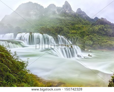 Ban Gioc Waterfall craggy limestone permissive side misty morning with grass and tones of lower cascade. It is considered most beautiful waterfalls in Southeast Asia and a national scenic Vietnam