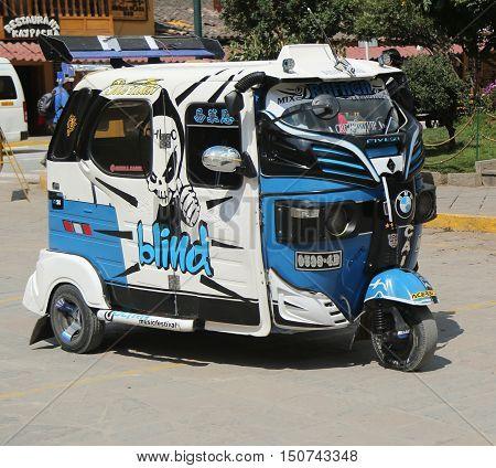 OLLANTAYTAMBO, PERU - OCTOBER 1, 2016: Auto rickshaw in the street of Ollantaytambo, Sacred Valley, Peru. Ollantaytambo was the royal estate of Emperor Pachacuti who conquered the region.