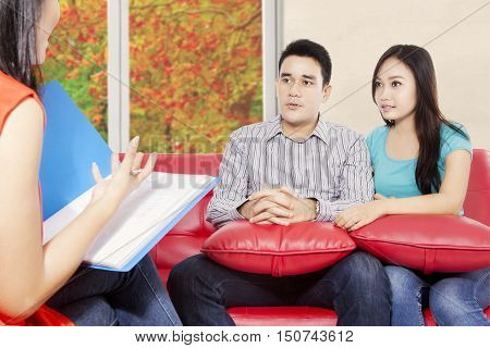 Portrait of husband and wife sitting in the red sofa and holding pillow while psychiatrist giving motivation for young couple autumn on the window