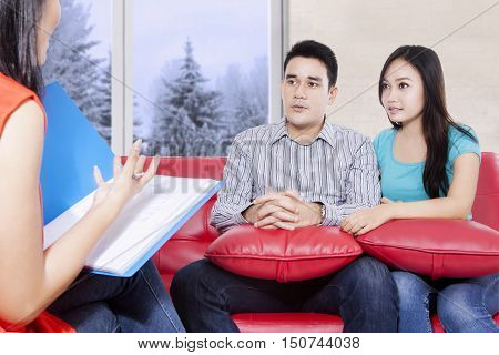 Young couple sitting on the red couch and listening while psychiatry explaining their problem. winter on the window