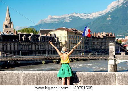 Young woman with french flag enjoying traveling in Grenoble city in France