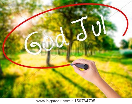 Woman Hand Writing God Jul  (merry Christmas In Swedish) With A Marker Over Transparent Board