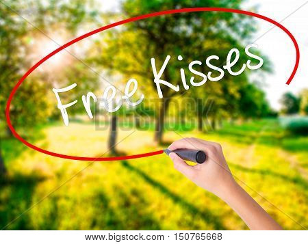 Woman Hand Writing Free Kisses  With A Marker Over Transparent Board