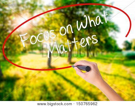 Woman Hand Writing Focus On What Matters With A Marker Over Transparent Board