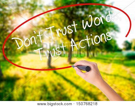 Woman Hand Writing Don't Trust Words, Trust Actions With A Marker Over Transparent Board