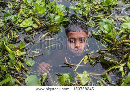 MUNSHIGANJ DHAKA- JULY 29 2016. An unidentified boy taking bath and play in water