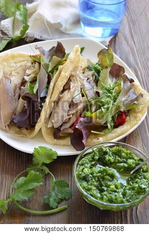 Tacos with chicken and vegetable salad with green sauce, vertical