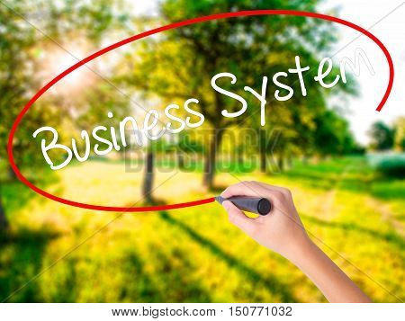 Woman Hand Writing Business System With A Marker Over Transparent Board .