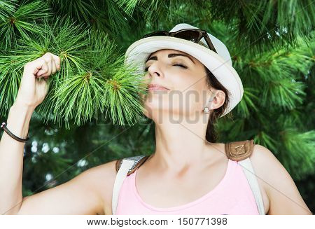 Young caucasian woman sniffs green needles of conifer tree in the park. Natural beauty. Positive emotions.