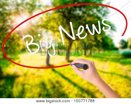 Woman Hand Writing Big News With A Marker Over Transparent Board