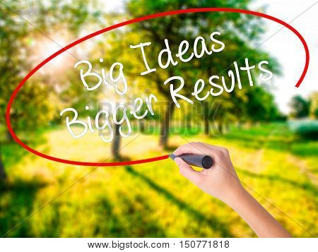 Woman Hand Writing Big Ideas Bigger Results  With A Marker Over Transparent Board