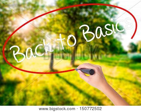 Woman Hand Writing Back To Basics With A Marker Over Transparent Board