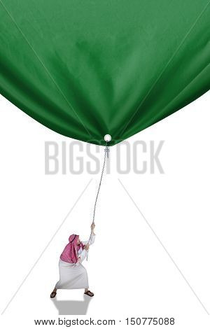 Image of a middle eastern person wearing islamic clothes and pulling a green banner isolated on white background