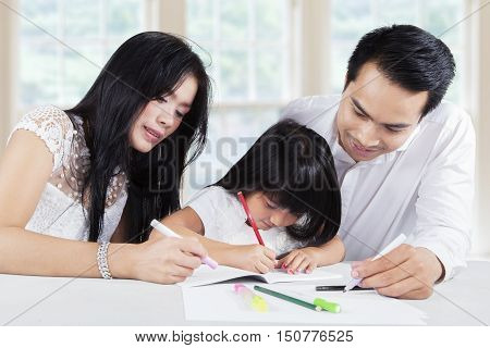 Photo of two young asian parents with black hair help their child for studying and doing homework at home