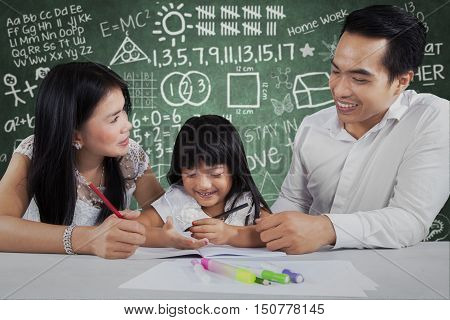 Portrait of cheerful family doing school assignment together on the table shot with scribble background on the blackboard
