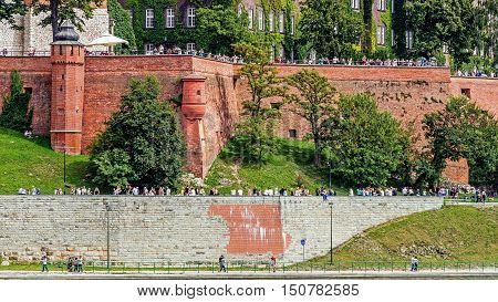 KRAKOW POLAND - AUGUST 15 2016: Tourists visit the Wawel Hill where the Royal Castle is located. In the background the Cathedral Basilica of St. Stanislaus and Wenceslas.