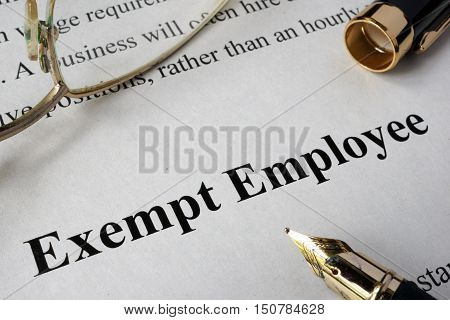 Exempt employee concept written on a paper.