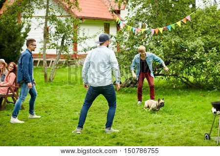 leisure, holidays, people and pets concept - happy friends playing with dog at summer garden party
