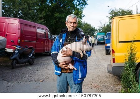 Kamianka Ukraine - September 29 2016: Native ukrainian peasant holds a cute piglet in his hands