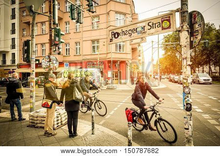 BERLIN GERMANY - OCTOBER 7 2016: motion view of everyday life with bikers and pedestrians at beginning of Box Hagener Strasse in the area of Friedrichshain at sunset - Warm vintage vignetted filter