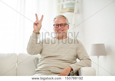 old age, gesture and people concept - smiling senior man in glasses sitting on sofa and showing v sign at home