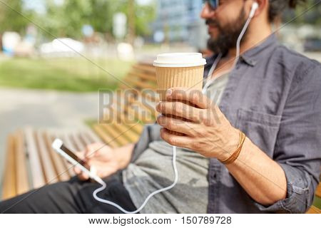 people, drinks, technology, leisure and lifestyle - close up of man with earphones and smartphone drinking coffee from disposable paper cup on city street bench