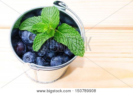 Fresh blueberries with mint in meta lbucket on wooden background