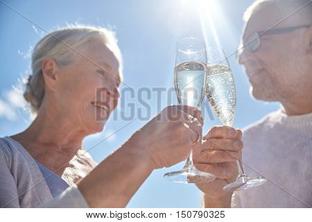 family, age, holidays, leisure and people concept - close up of happy senior couple clinking champagne glasses on summer beach